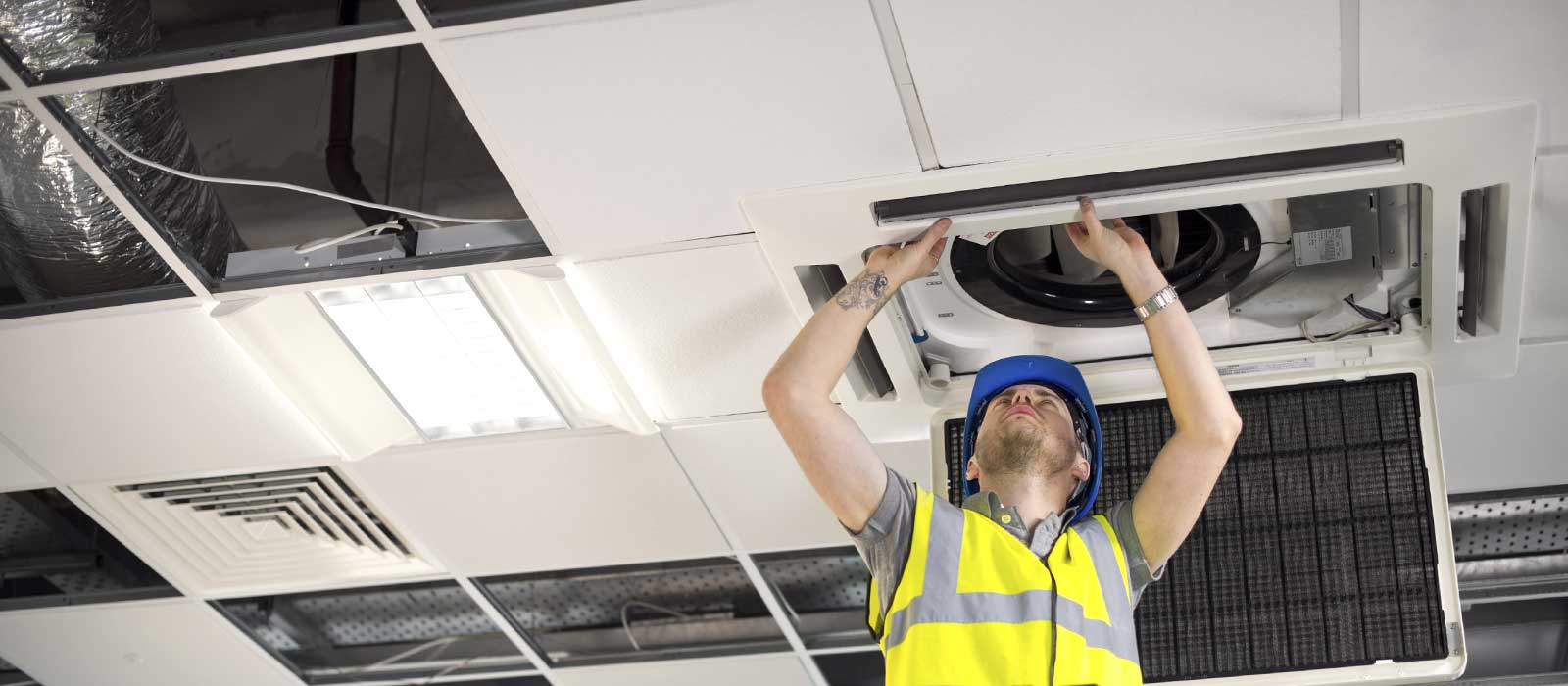Engineer working on ceiling air conditioning duct : HVAC Services North West